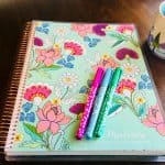 teacher lesson planner, pens, and coffee mug on table