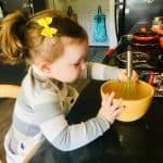 montessori child stirring eggs in bowl with whisk