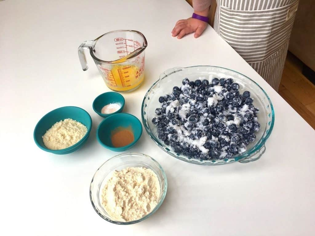 blueberry mixture in pie dish with cake and ingredients in bowls