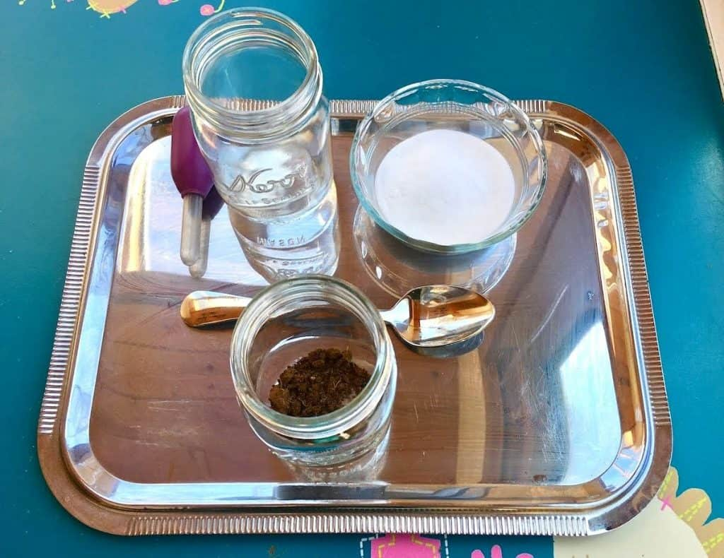 DIY Soil pH Testing Tray with dropper, mason jar of water, mason jar of baking soda, mason jar of soil, and a spoon
