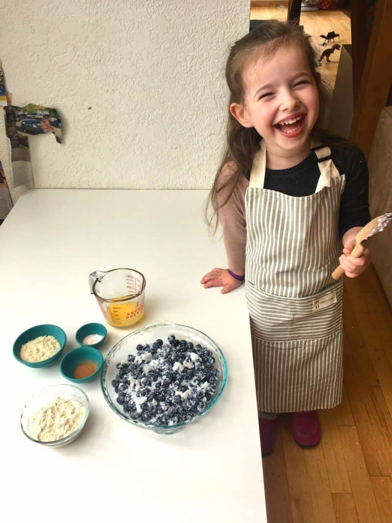 Montessori child enjoying the taste of the blueberry mixture.