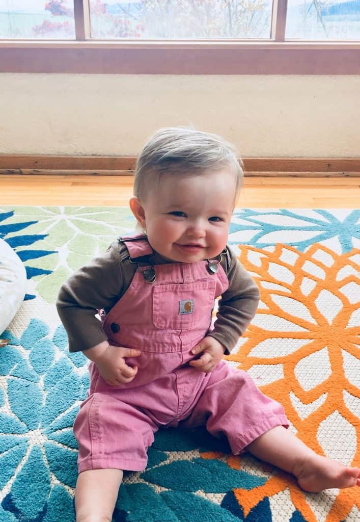 montessori baby sitting on the floor and smiling