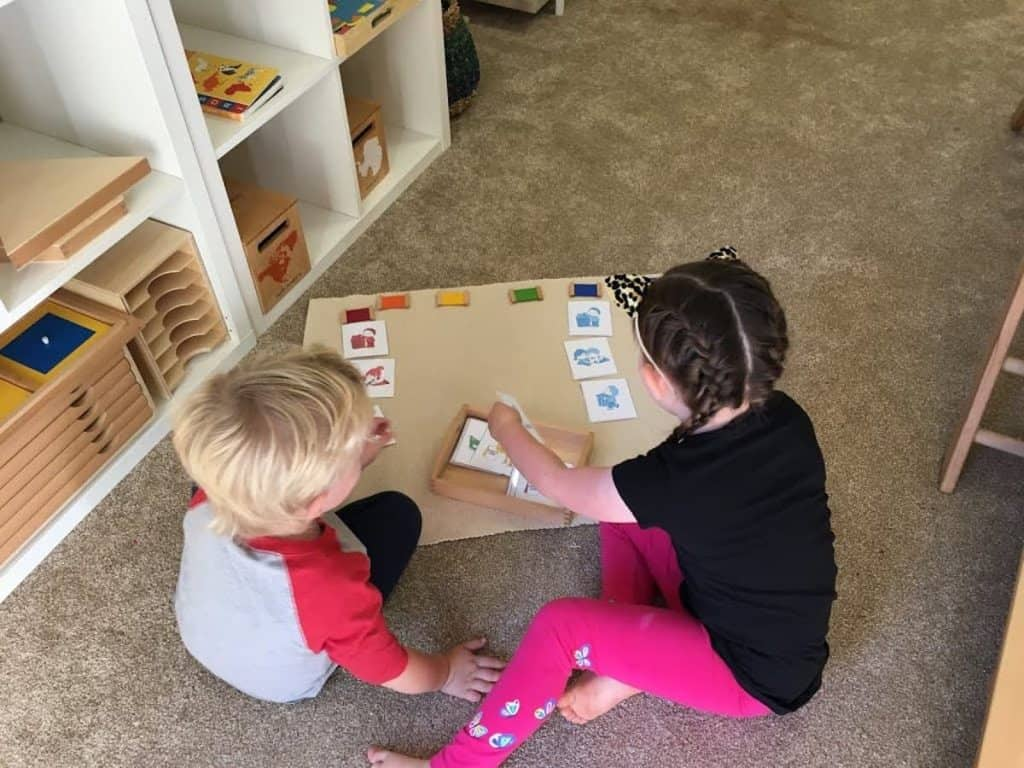 Montessori children sorting grace and courtesy cards together
