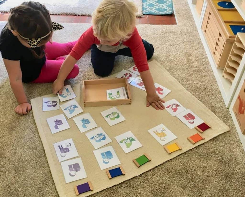 montessori children working on Grace and Courtesy themed color sorting sensorial shelf work