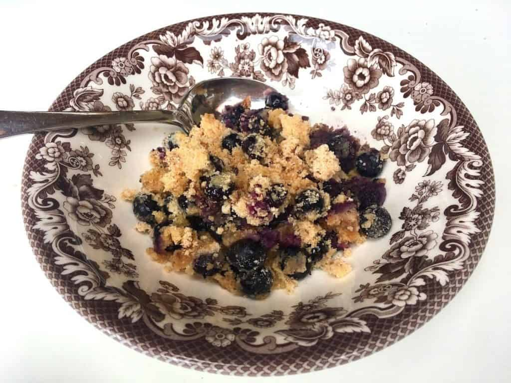 Blueberry Dump Cake in bowl with spoon.