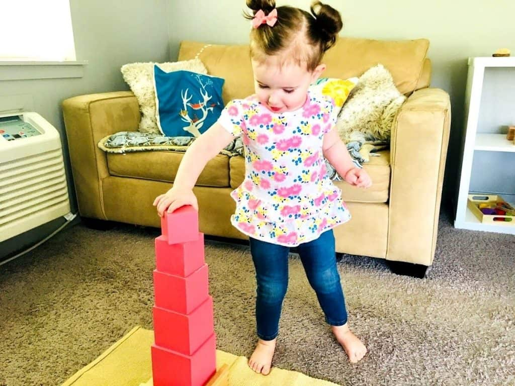 Child building the Montessori Pink Tower on mat in homeschool