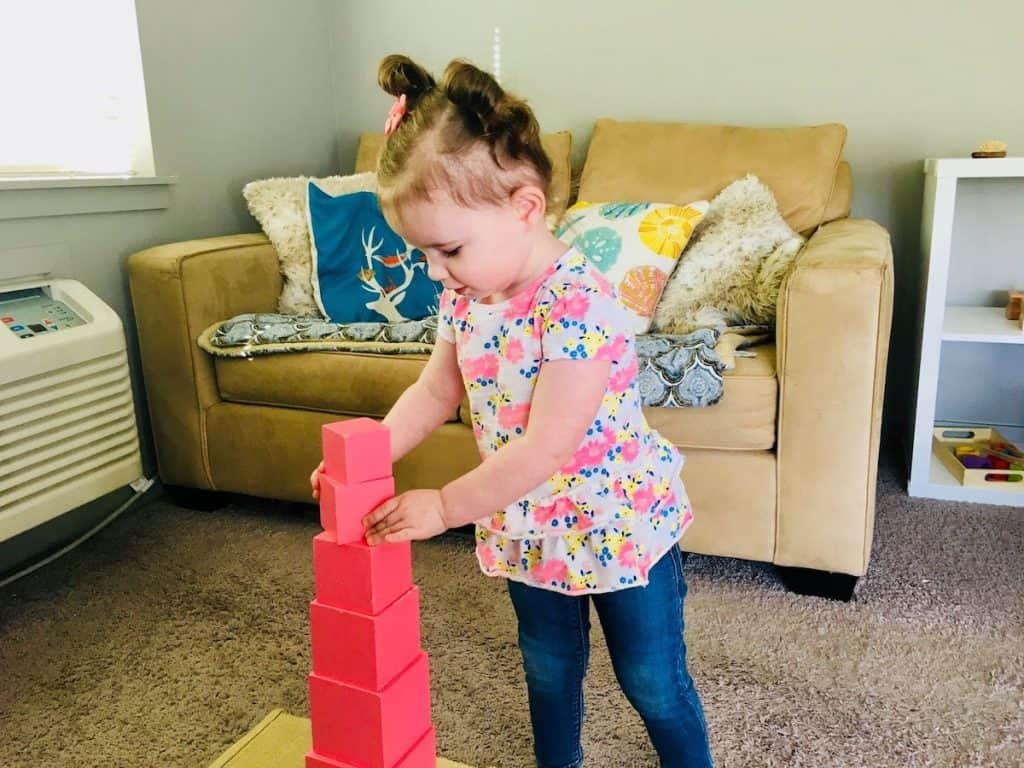 Child straightening the Pink Tower cubes