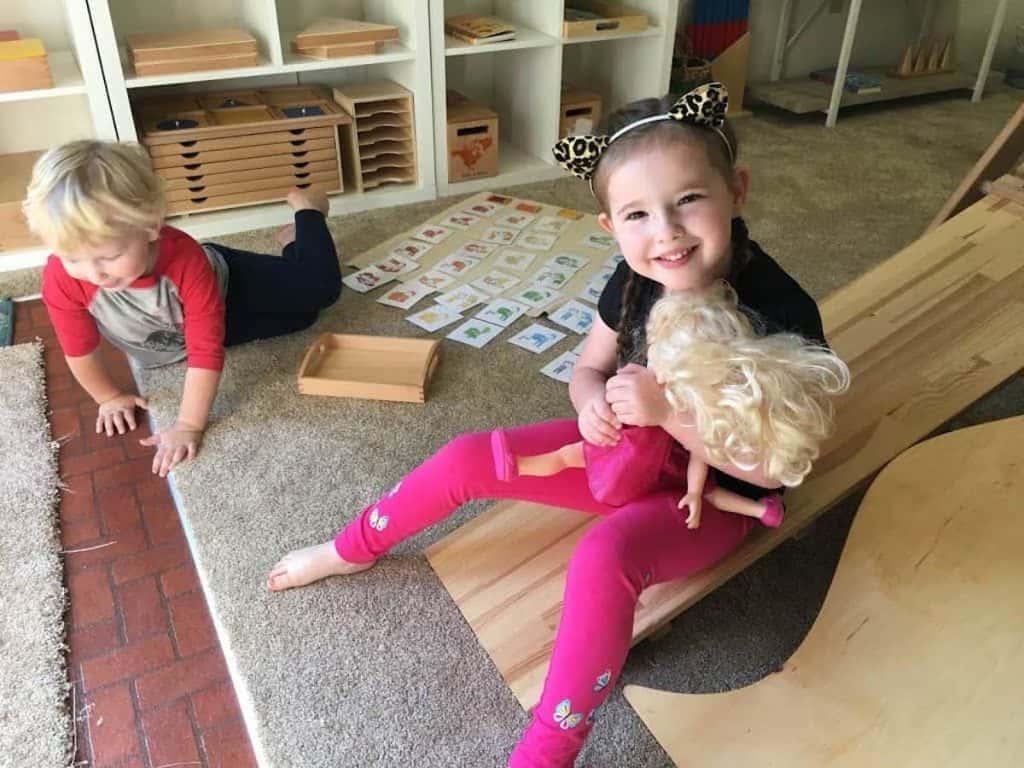 Montessori child holding doll and sitting on an indoor slide next to another child on the floor
