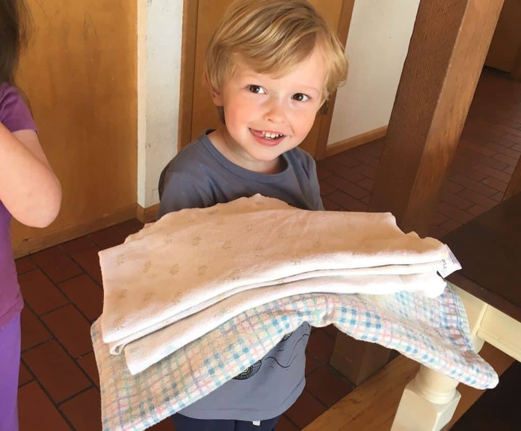 Montessori child holding blankets for Practical Life Montessori Pets and Caring for Animals routine