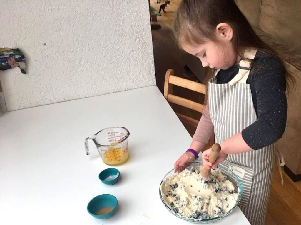 Montessori child stirring cake mixture with wooden spoon