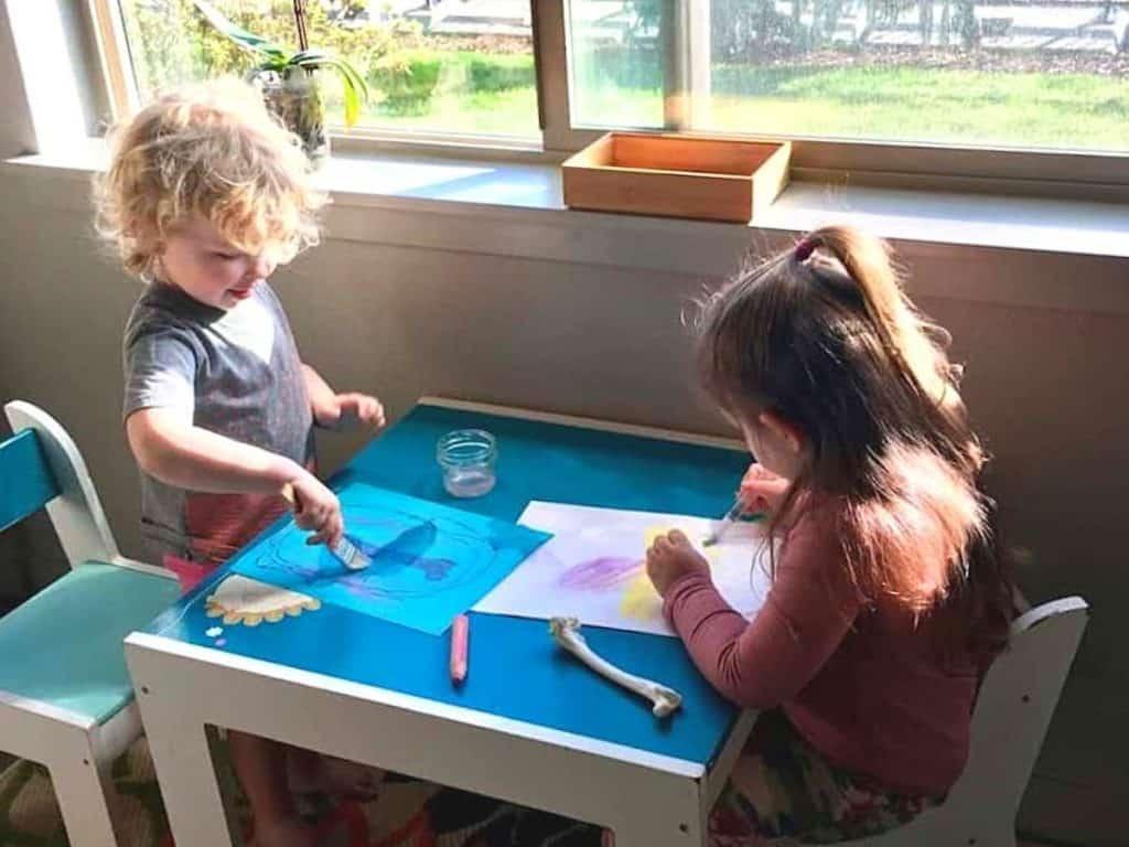 Montessori kids painting animal bone tracing with watercolor crayons for Montessori Geology & Paleontology Unit Study