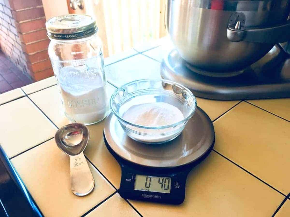baking soda in dish sitting on kitchen scale next to measuring spoon and mason jar