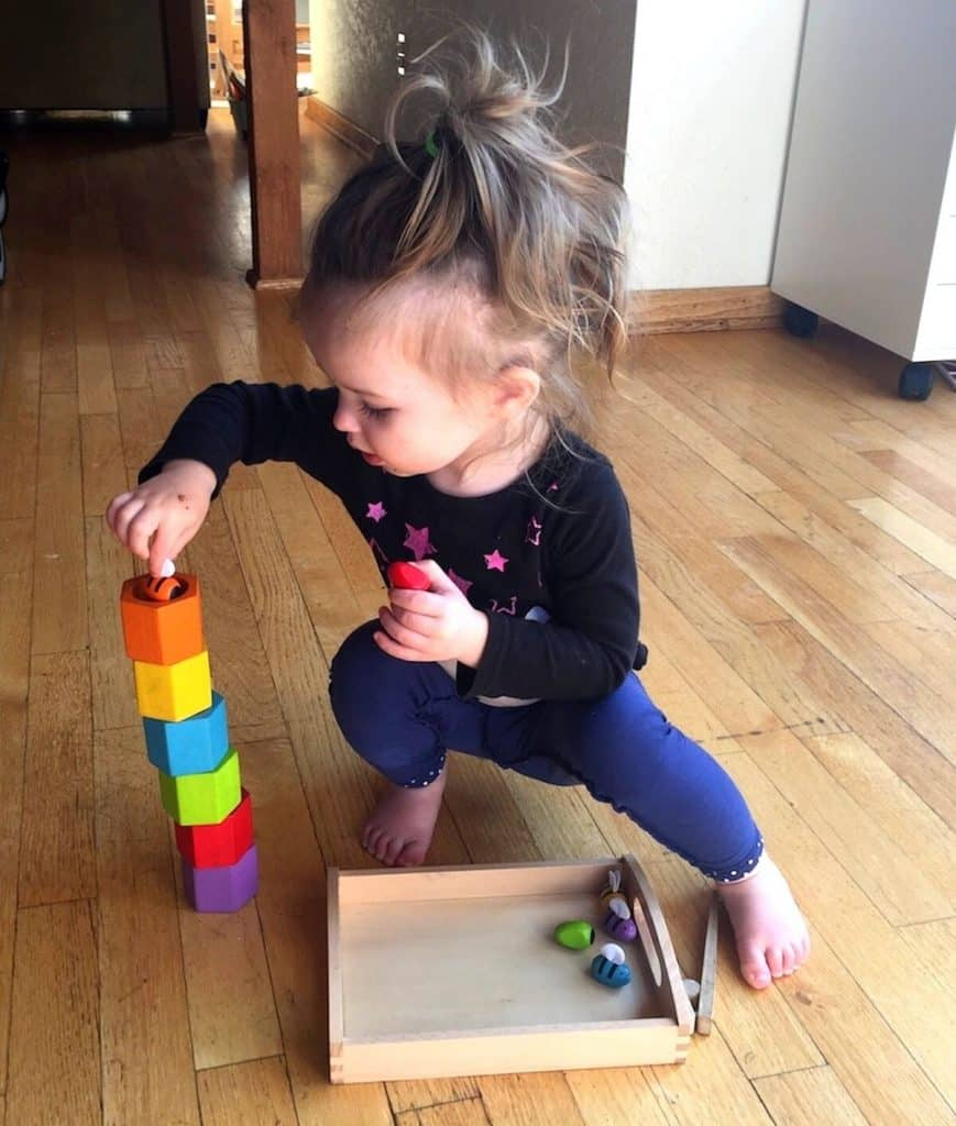 Montessori child placing small bee manipulative in matching colored beehive
