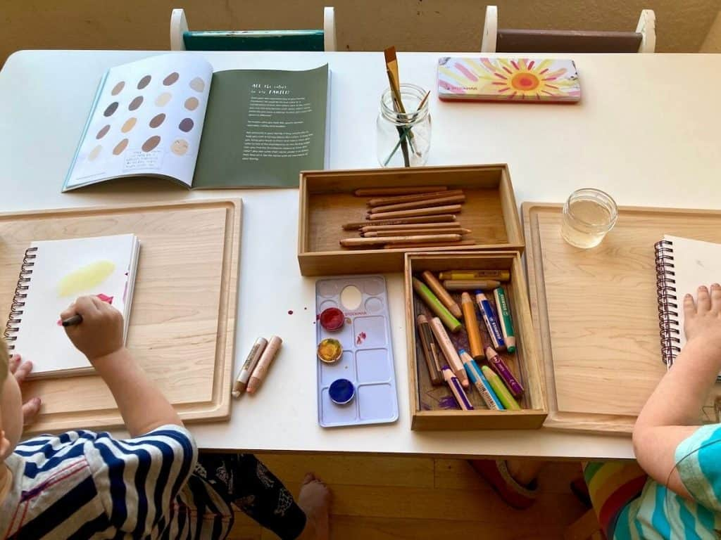 art supplies and tools on a table with two children