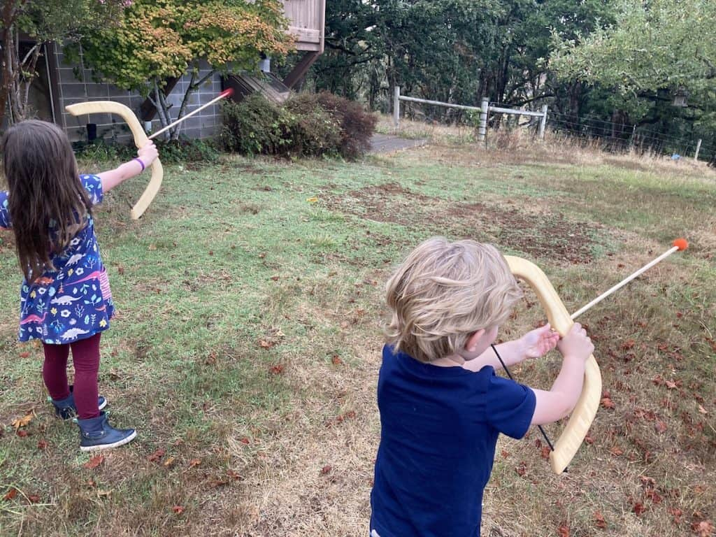 children using toy bow and arrows