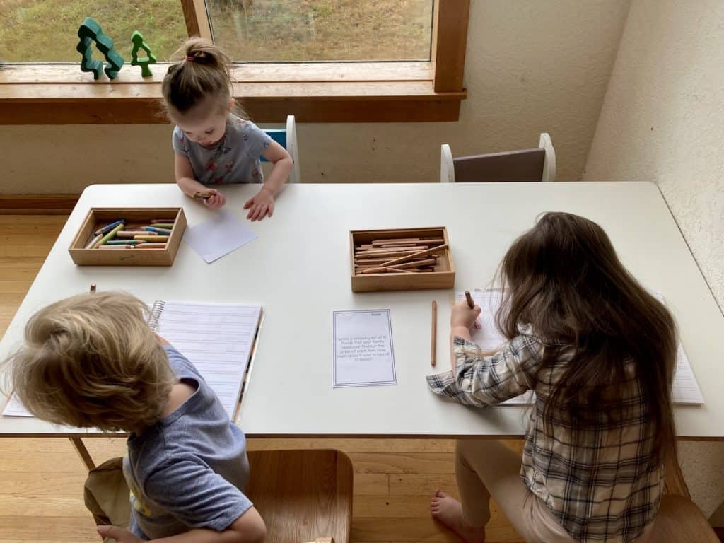 three children sitting at a table with paper, crayons, and pencils